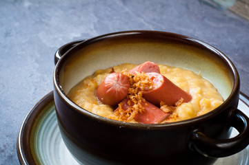 Bowl of yellow split pea soup with chopped hot dog sausage and fried onion. A popular Scandinavian dish served on a slate table.