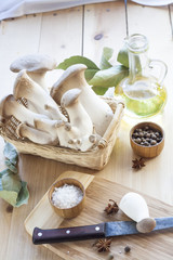 Basket with mushrooms, olive oil and ingredients for cooking on the wooden table of the kitchen background