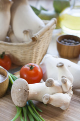 Eryngii mushrooms, olive oil and ingredients for cooking on the wooden table of the kitchen background