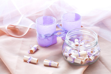 Dreams written on a white rolled paper in a glass jar and two aromatic candles in glass candlesticks with lavender paper