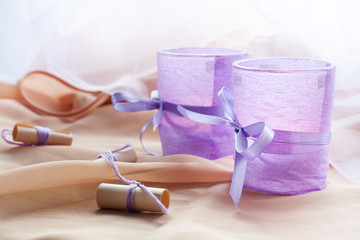 Two aromatic candles in glass candlesticks with lavender paper on table close up