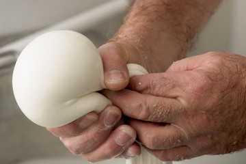 close up of hands doing a mozzarella in a dairy