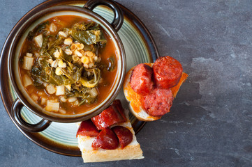 Kale, pearl barley and tomato soup served with crusty bread topped with chunks of chorizo sausage. Presented in a rustic bowl on a slate stone table.