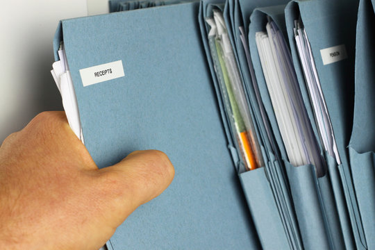 Man taking file folder / Man taking a file in an office.
