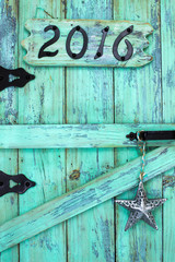 Year 2016 in black iron numbers and silver tin star hanging on antique rustic  wood door