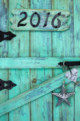 Year 2016 and tin star and heart hanging on rustic door