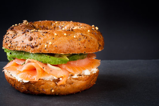 Healthy freshly baked bagel filled with smoked salmon lox and topped with avocado. Served on a gray slate table against a dark background.