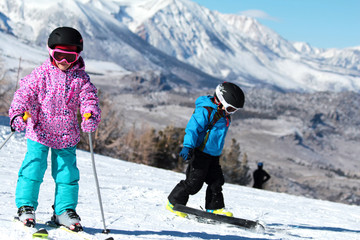 Little Skiers Love Big Mountains. Picture of  little skiers in a mountain ski against the backdrop of snow-capped mountains