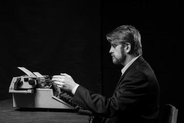 writer, man in a black jacket typing on typewriter