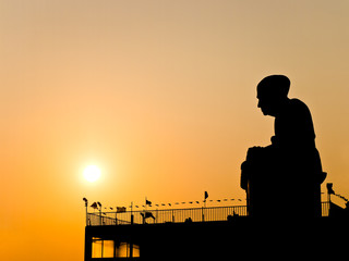 Silhouette view of Buddhist monk statue with twilight sun