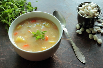 Bowl with bean soup and metal spoon