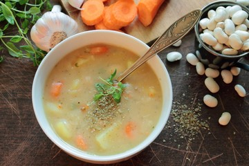 Bowl with bean soup and herbs