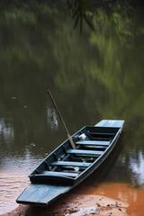 boat in still river water at Kaeng Bangrachan, Thailand