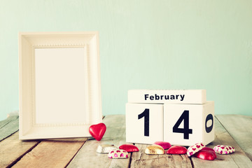 February 14th wooden vintage calendar with colorful heart shape chocolates next to blank vintage frame on wooden table. selective focus.Template ready to put photography. retro filtered