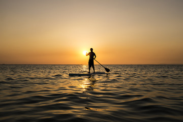 Man paddling while standing on a surfboard in the sunset, Otres Beach, Cambodia.