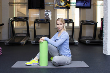 beautiful blond athletic girl in a gym doing exercises. accessories, fitness equipment