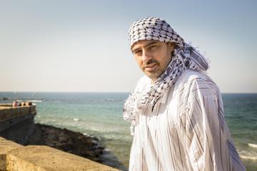 Arab man wearing Keffiyeh Seating Near The Beach