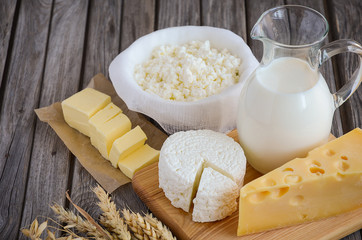 Fresh dairy products. Milk, cheese, butter and cottage cheese with wheat on the rustic wooden background. Horizontal permission. Selective focus.