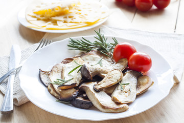 Fried eryngii mushrooms with fresh rosemary in white plate on wooden background