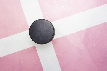 old hockey puck is on the ice with denmark flag