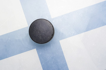 old hockey puck is on the ice with finland flag