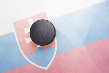 old hockey puck is on the ice with slovakia flag