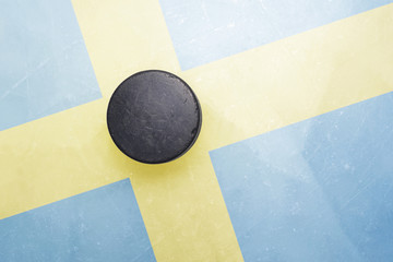 old hockey puck is on the ice with sweden flag