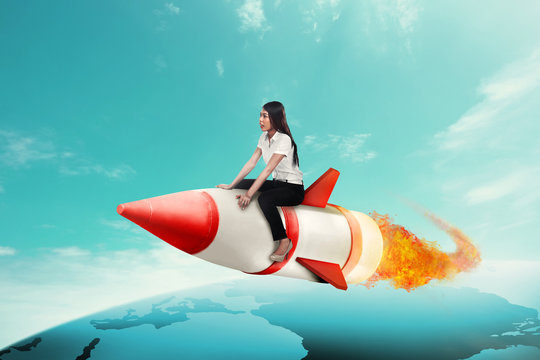 Business woman riding rocket across the earth