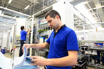 Mitarbeiter in einer Elektronikfabrik kontrolliert techn. Unterlagen zur montage von Bauteilen