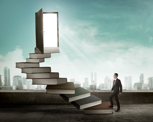 Asian business man stepping up stair made from book