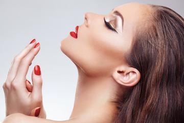 Closeup of beautiful woman face with nice makeup and red nails