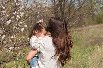 Mom kisses and hugs daughter on nature, family, motherhood, child