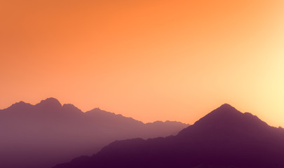 Orange and yellow sunset above layers of mountains.