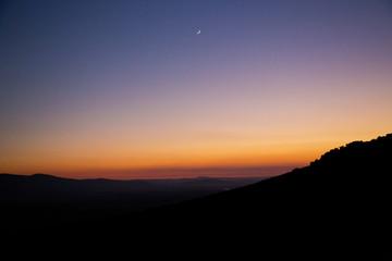 Atardecer / atardecer con degradación de colores desde anaranjados hasta azul oscuro y silueta de montaña en la parte inferior.