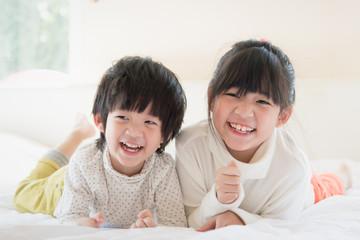 asian children lying on white bed