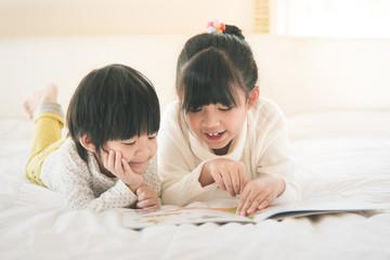 asian children reading book on white bed