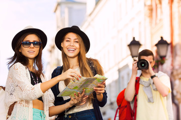 Girls together hold city map and guy shooting