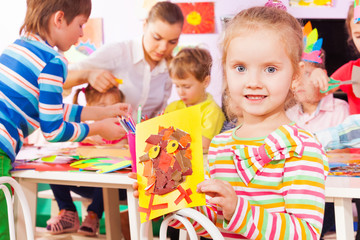 Girl hold picture and kindergarten class on back
