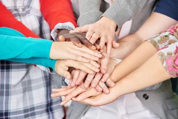 Schüler stapeln ihre Hände zusammen