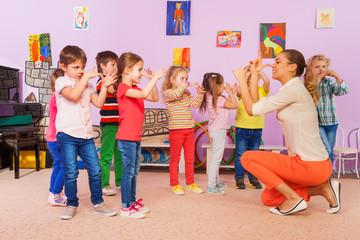 Kids repeat after teacher gesture in class