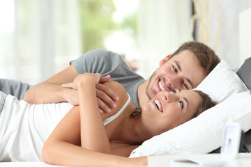 Couple flirting on a bed at home
