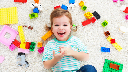 happy child laughing and playing with toys constructor