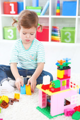 child girl playing with toys and builds constructor
