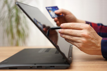 man is using debit or credit card to pay online on portable touc