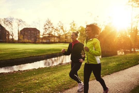 Two sportswomen running in park