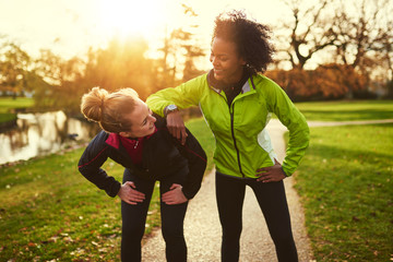 Two sportswomen relaxing after jogging Wall mural