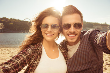 Two lovers making a selfie photo near the river, close-up photo