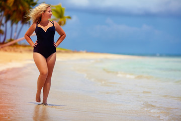 beautiful plus size woman walking on summer beach