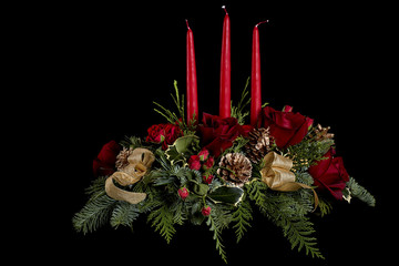 Decorative flower arrangement with roses, red candles, gold pine cones and evergreen needles isolated on black