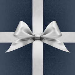 Shiny silver satin ribbon bow on blue background